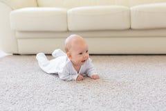 Kinderjaren, kleutertijd en mensenconcept - weinig babyjongen of meisje die op vloer thuis kruipen royalty-vrije stock foto's