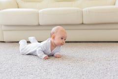 Kinderjaren, kleutertijd en mensenconcept - weinig babyjongen of meisje die op vloer thuis kruipen royalty-vrije stock afbeeldingen