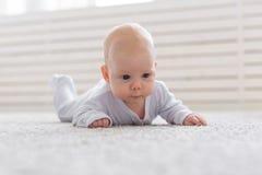 Kinderjaren, kleutertijd en mensenconcept - weinig babyjongen of meisje die op vloer thuis kruipen stock foto's