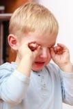 Kinderjaren Portret van het ongelukkige schreeuwende jonge geitje van het jongenskind thuis stock afbeeldingen