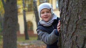 Kinderjaren, seizoen en mensenconcept - het mooie meisje verbergen achter boom in de herfst stock footage