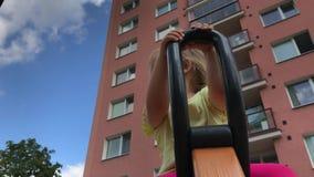 Kinderjaren in stad: glimlachende peuter op het spinnen rit bij high-rise blokken stock videobeelden
