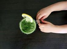 Kinderjunge übergibt das Halten des gesunden Spinatsgrüns Gemüsesmoothie als gesundes Sommergetränk mit Bestandteilen auf Holztis lizenzfreies stockbild