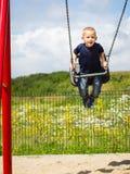 Kinderjunge, der auf dem Schwingen im Freien spielt Lizenzfreies Stockfoto