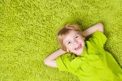 Kinderjunge, der auf grünem Teppichhintergrund liegt Lächelndes Kind Lizenzfreie Stockbilder