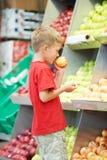 Kinderjunge, der das Fruchtgemüseeinkaufen macht Lizenzfreies Stockfoto