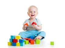 Kinderjunge, der hölzerne Spielwaren spielt Stockfotografie