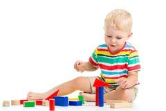 Kinderjunge, der hölzerne Spielwaren spielt Stockfotos