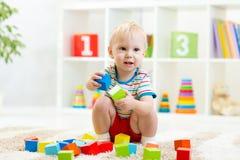 Kinderjunge, der hölzerne Spielwaren spielt Lizenzfreies Stockfoto