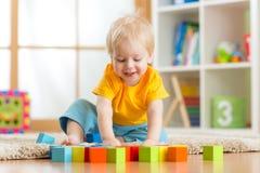 Kinderjunge, der hölzerne Spielwaren spielt Lizenzfreie Stockbilder