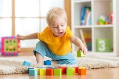 Kinderjunge, der hölzerne Spielwaren spielt Stockbilder