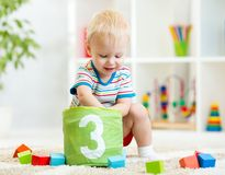 Kinderjunge, der Holzklotzspielwaren spielt Stockbilder