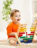 Kinderjunge, der mit Abakus spielt Lizenzfreie Stockfotografie