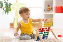 Kinderjunge, der mit Abakus spielt Stockbild