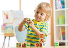 Kinderjunge, der mit Blockspielwaren spielt und Buchstaben lernt Stockfotos