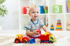 Kinderjunge, der mit Spielzeugauto spielt Lizenzfreies Stockfoto