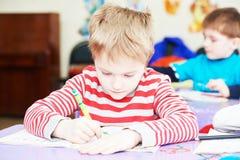 Kinderjunge, der Schreiben studiert Stockfotografie