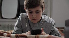 Kinderjunge, der zu Hause mit Handy mit Kopfhörern spielt Kind unter Verwendung Smartphones beim Lügen auf einem Bett stock video
