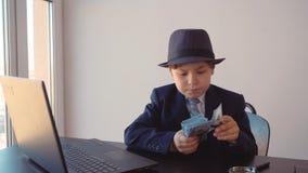 Kinderjunge sieht wie ein Geschäftsmann im Hut aus und Anzug überprüft Dollar mit Vergrößerungsglas stock footage