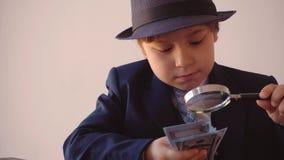 Kinderjunge sieht wie ein Geschäftsmann im Hut aus und Anzug betrachtet Dollar mit Vergrößerungsglas stock footage