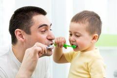 Kinderjunge und bürstende Zähne des Vatis im Badezimmer Lizenzfreie Stockfotos