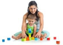 Kinderjunge und -mutter spielen zusammen mit Blockspielwaren Stockfotografie