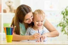 Kinderjunge und -mutter zeichnen mit bunten Bleistiften Lizenzfreie Stockfotos