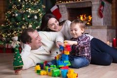 Kinderjunge und seine Eltern, die mit Blockspielwaren unter dem Weihnachtsbaum spielen Stockfoto