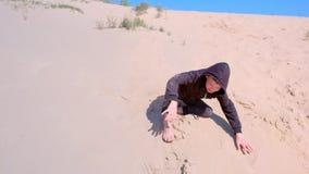 Kinderjunge vernachlässigt Rollen die Sanddünen auf Strand an den Ferien stock footage