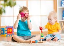 Kinderjungen, die mit pädagogischen Spielwaren spielen Lizenzfreie Stockfotos
