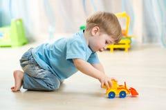 Kinderjungenkleinkind, das mit Spielzeugauto spielt Stockbild