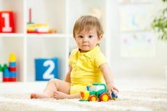Kinderjungenkleinkind, das mit Spielzeugauto spielt stockfoto