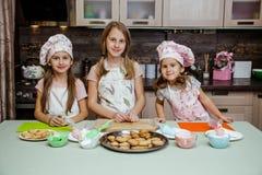 Kinderküchenmädchen kochen Kappencreme-Cremedekor mit drei Schwestern der Plätzchen des Schutzblechkleinen kuchens kleinen lustig lizenzfreies stockfoto