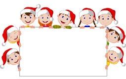 Kinderkarikatur mit einem leeren Zeichen und Weihnachtshüten Stockfotografie