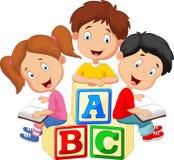 Kinderkarikaturlesebuch und -sitzen auf Alphabetblöcken Stockfotos