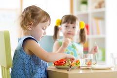 Kinderkinder, die Gemüse im Kindergarten oder zu Hause essen stockfotografie
