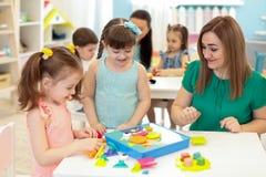 Kinderkinder, die mit Erbauer auf Tabelle im Kindergarten spielen lizenzfreie stockbilder