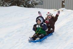 Kinderkinder, die Tobogganschlitten-Schneewinter rodeln Lizenzfreies Stockfoto