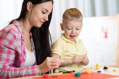 Kinderkinderjunge und -mutter spielen buntes Lehmspielzeug an der Kindertagesstätte oder am Kindergarten Lizenzfreie Stockfotografie