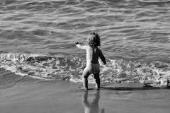 Kinderkindheits-Kinderglück-Konzept Kleiner Junge im Meerwasser Lizenzfreies Stockfoto