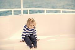 Kinderkindheits-Kinderglück-Konzept Kleiner Kinderjunge mit dem netten Gesicht, das in der Yacht sitzt Stockfotos