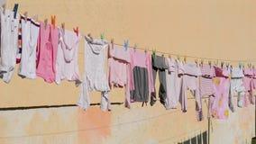 Kinderkleidung, die draußen trocknet stock video footage