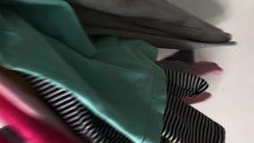 Kinderkleidung wird auf weiße Tabelle geworfen Zeitlupevideo Konzept der Reinigung, Kleidung wählend, Auftrag, Raumorganisation stock video