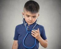 Kinderkleiner Junge, der auf sein Herz mit Stethoskop hört Lizenzfreies Stockbild