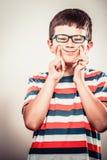 Kinderkleiner Junge, der dummen Gesichtsausdruck macht Stockfotografie