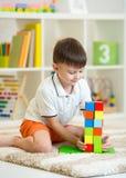Kinderkleiner Junge, der mit den Würfeln, lächelnd spielt Stockfoto