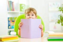 Kinderkleines Mädchen, das hinter Buch sich versteckt Stockfoto