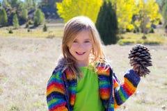 Kinderkleines Mädchen, das Kiefernkegel im Winterfall anhält Stockfotografie