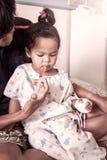 Kinderkleines Mädchen erhält Medizin mit einer Spritze in ihrem Mund Lizenzfreies Stockbild