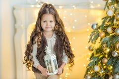 Kinderkleines Mädchen mit Geschenkbox nahe Weihnachtsbaum und Kamin zu Hause Stockfotos